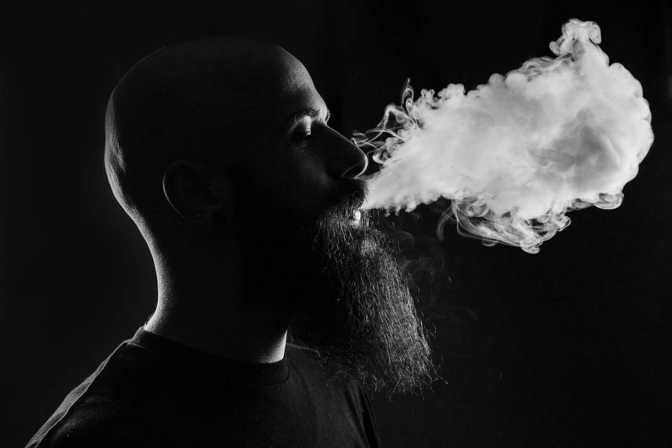 man exhaling marijuana smoke