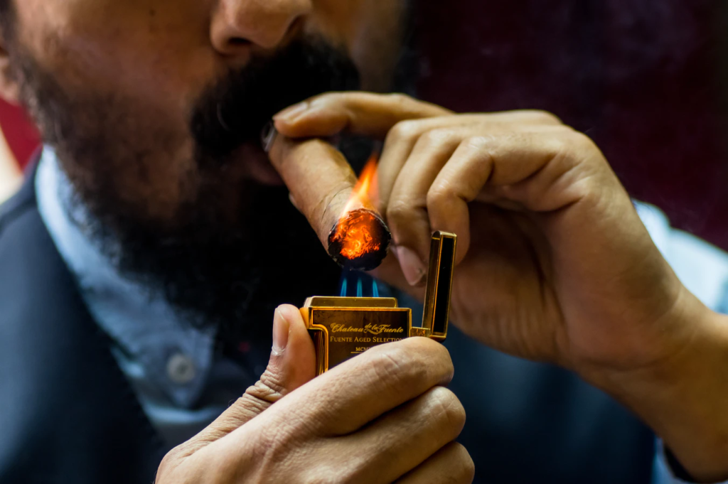 man lighting a cigar wondering how to roll a backwood blunt